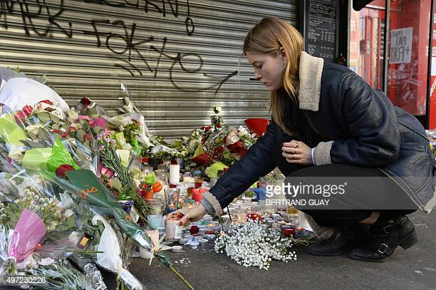 A woman places down a candle on November 15 2015 at a memorial site outside of the Le Belle Equipe in the 11th district of Paris for victims of the...