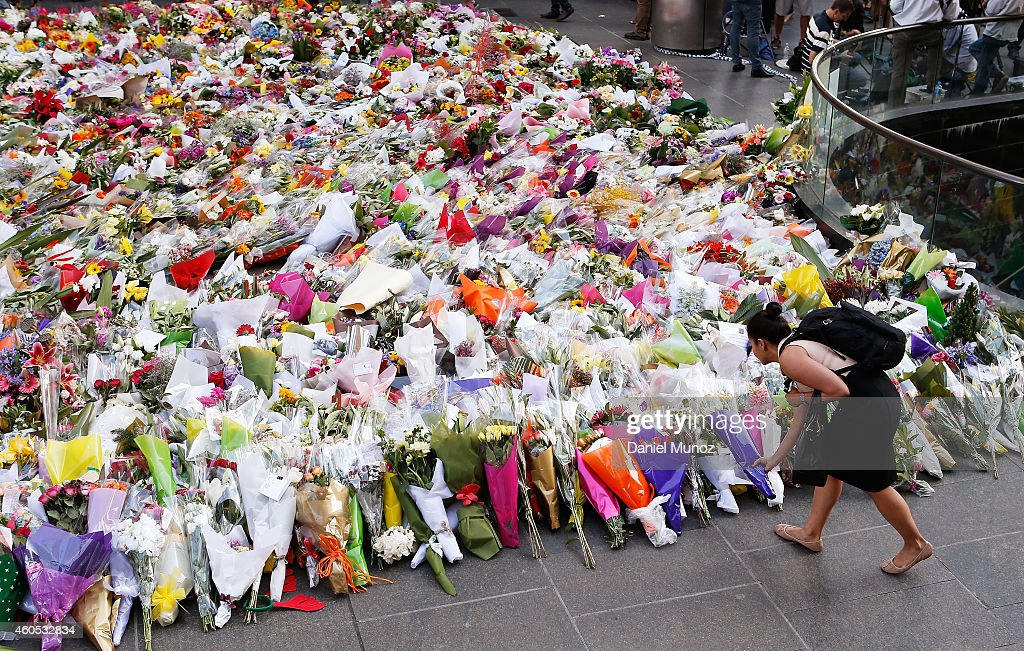 A woman places flowers as a mark of respect for the victims of Martin Place siege on December 16 2014 in Sydney Australia Sydney siege gunman Man...