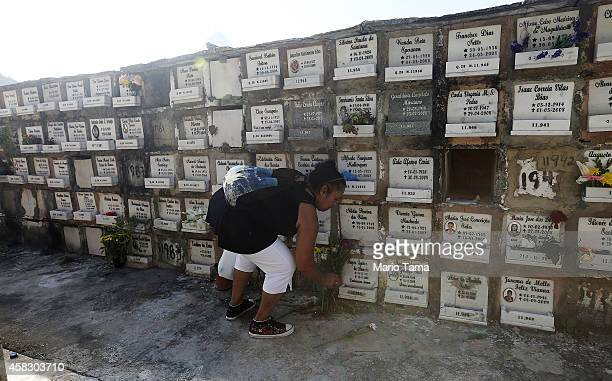 A woman places flowers at a crypt during Day of the Dead festivities at Sao Joao Batista cemetery on November 2 2014 in Rio de Janeiro Brazil...