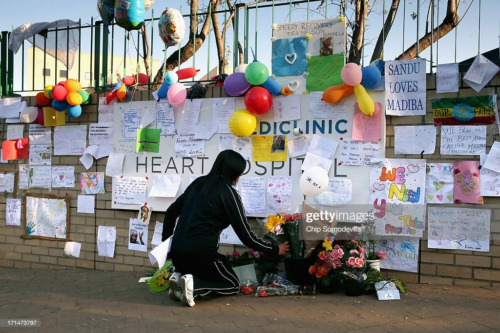 A woman places flowers at the base of the wall bearing dozens of hand-made messages of support for former South African President Nelson Mandela outside the Mediclinic Heart Hospital June 25, 2013 in Pretoria, South Africa. South African President Jacob Zuma confirmed Sunday that Mandela's condition has become critical since he was admitted to the hospital over two weeks ago for a recurring lung infection.