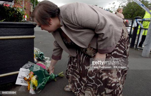 A woman places flowers close to the scene of a suspected gas blast in Buckley Street in the Shaw area of Oldham Greater Manchester in which...