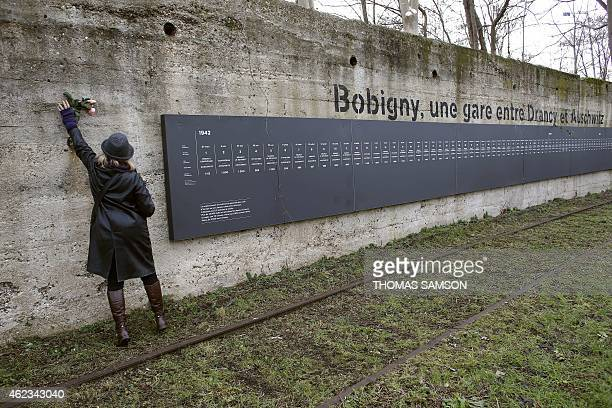 A woman places flowers near a commemorative plaque near a former train station in Bobigny northeast of Paris on January 27 from which Jews were...