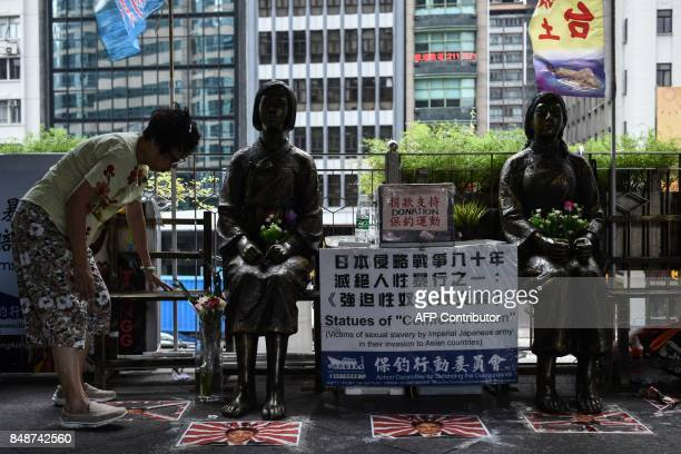 A woman places flowers next to two 'comfort women' statues ahead of a protest to mark the 86th anniversary of the 'Mukden Incident' in Hong Kong on...