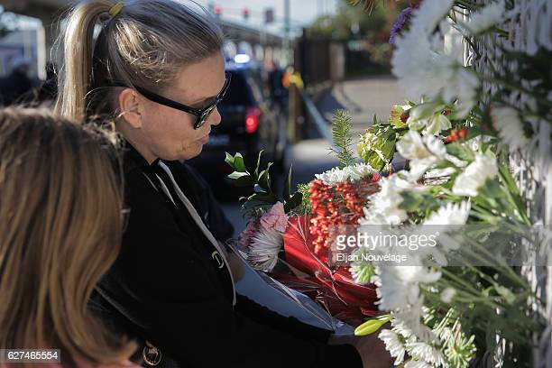 A woman places flowers on a fence outside a police line following an overnight fire that claimed the lives of at least nine people at a warehouse in...