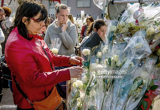 A woman places flowers on a playground gate as thousands of people pay their respect on April 18 2015 to nineyearoldgirl Chloe who was raped and...