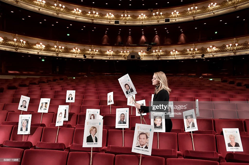 A woman places images of actors at their assigned seats during the annual BAFTA heads on sticks photocall at The Royal Opera House on February 11, 2015 in London, England. The seating plan is set ahead of the British Academy Film Awards 2015 which takes place on Sunday February 14, 2015.