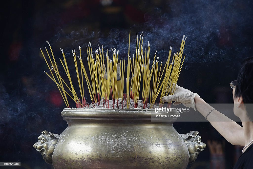 A woman places incense at Pak Tai Temple, on the first day of the Cheung Chau Bun Festival on May 14, 2013 in Hong Kong, Hong Kong. Today is the start of the Cheung Chau Bun Festival which will run until 17 May and celebrates the eight day of the fourth moon in the Chinese calendar.