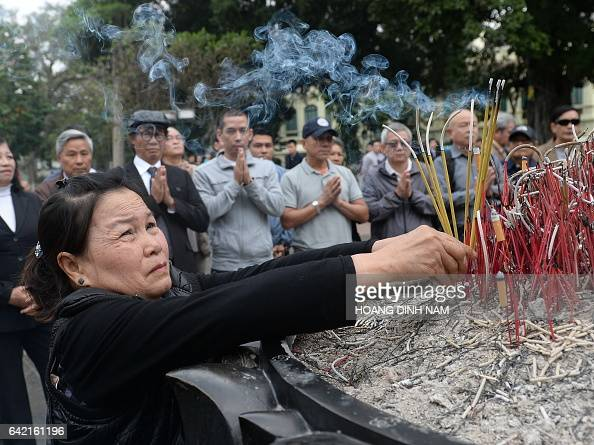 A woman places incense sticks as people stand praying during a small rally marking the 38th anniversary of the Chinese war border against Vietnam in...