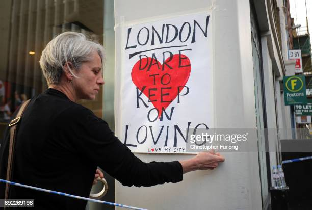 A woman places posters around the city near the scene of last night's terrorist attack on June 4 2017 in London England Police continue to cordon off...