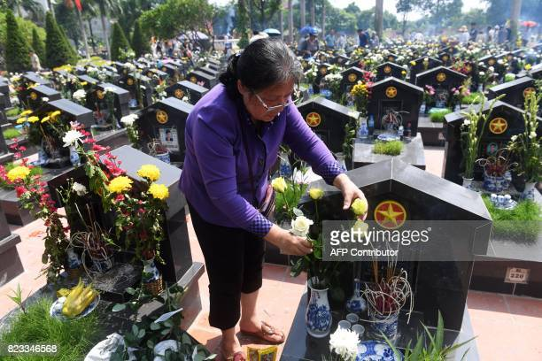 A woman places roses on the grave of a relative at an official cemetery in Hanoi on July 27 as Vietnam marks the National Day for war martyrs and...
