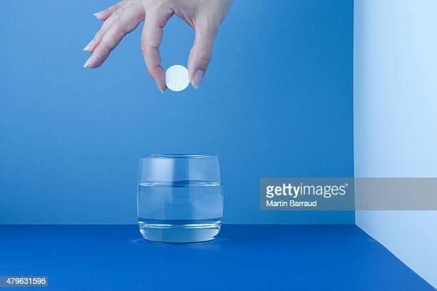 Femme en plaçant une tablette dans un verre d'eau