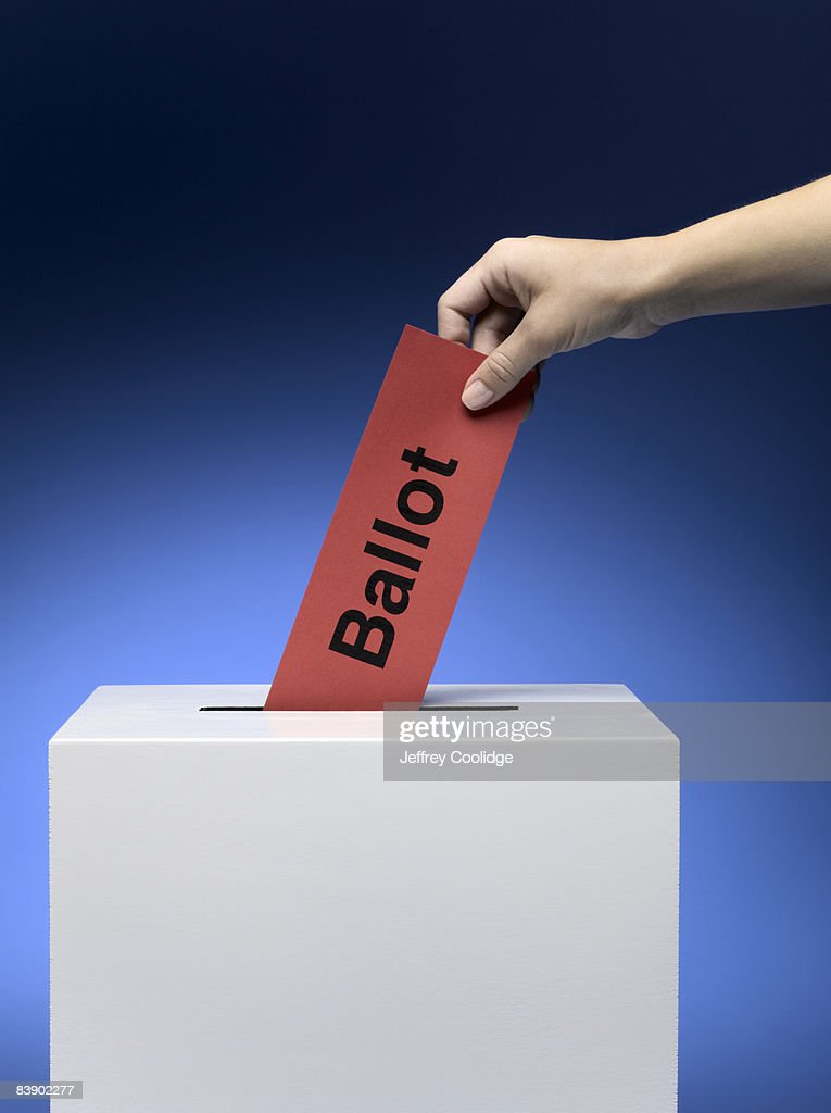 Woman placing ballot in ballot box : Stock Photo
