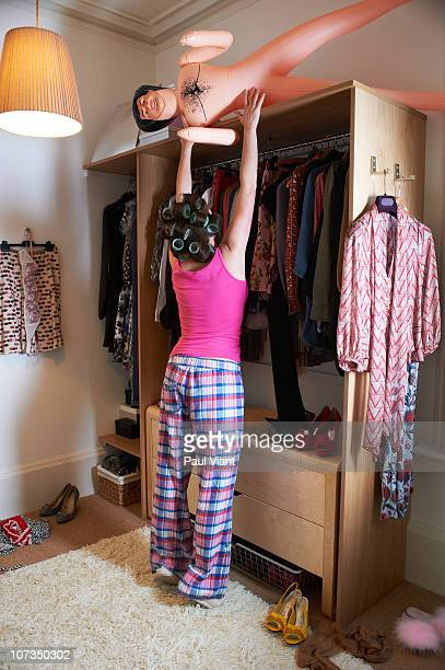 woman placing blowup doll on top of wardrobe
