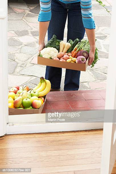 Woman placing cardboard box with vegetables at front door, mid section