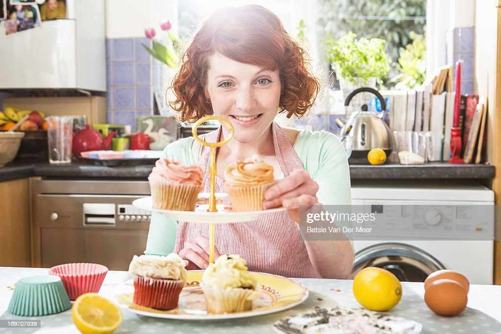 Woman placing cupcake on plate in kitchen. : Stock Photo