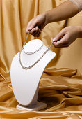 Woman placing diamond necklace on jewelry stand, studio shot