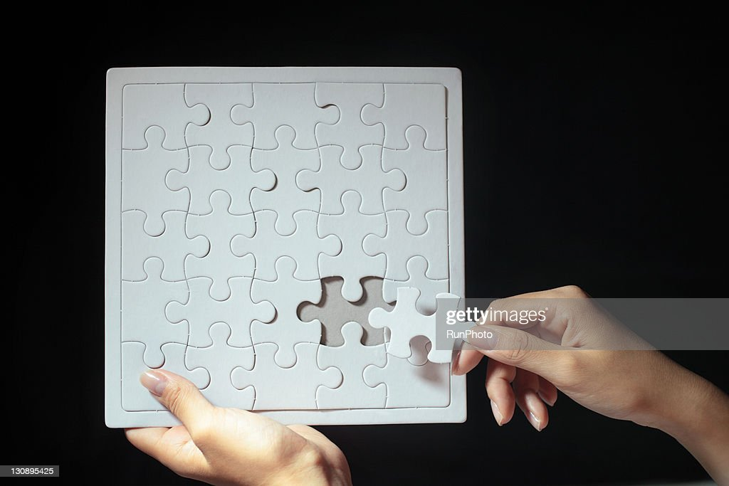 woman placing final puzzle piece,hands close-up : Stock Photo