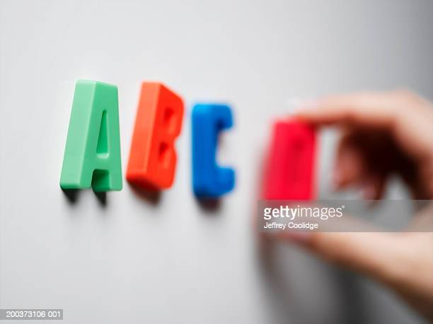 Woman placing magnetic letters on board, close-up