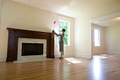 Woman placing orchid on fireplace in empty room