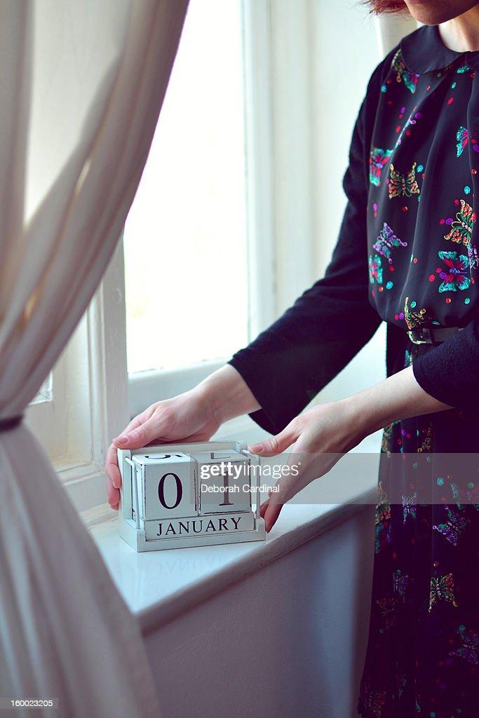 Woman placing perpetual calendar on windowsill : Stock Photo
