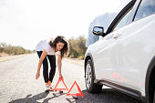 Woman placing emergency warning triangle sign on road by her broken car