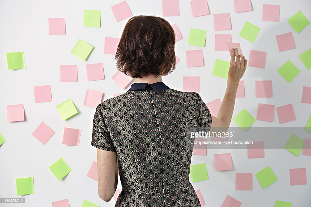 Woman placing sticky notes on board : Stock Photo