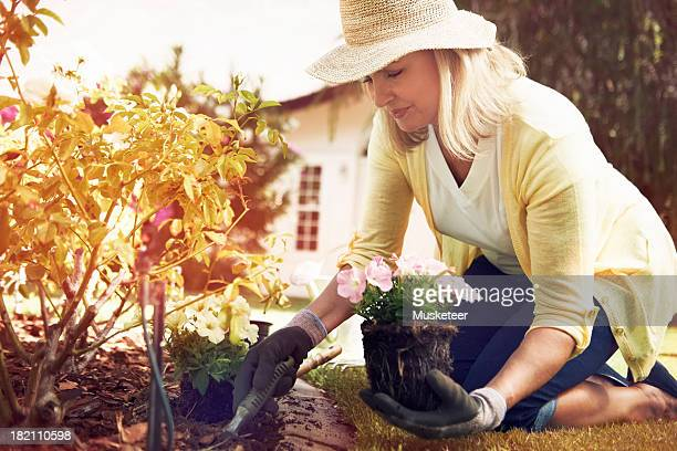 Woman planting flowers in her backyard