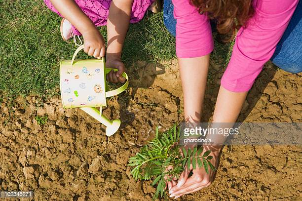 Woman planting with her daughter