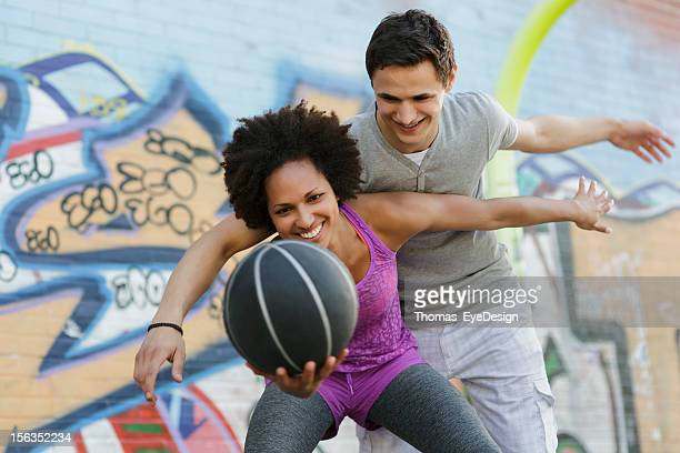 Woman Playing a Game of Basketball Against Man