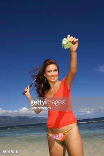 Woman playing badminton on beach