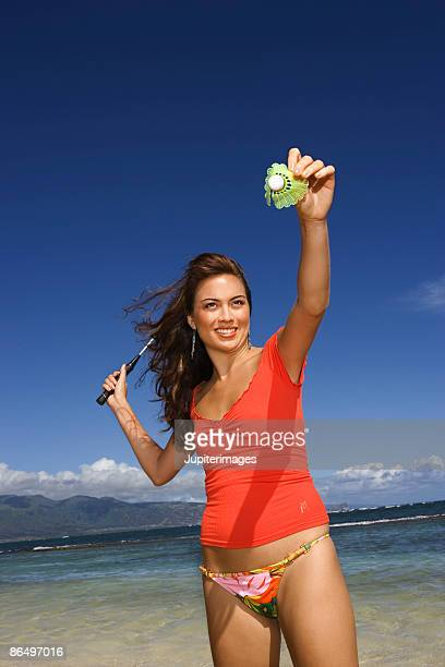 Woman playing badminton on beach