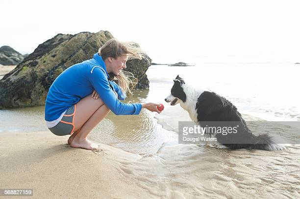 Woman playing ball with dog at beach.