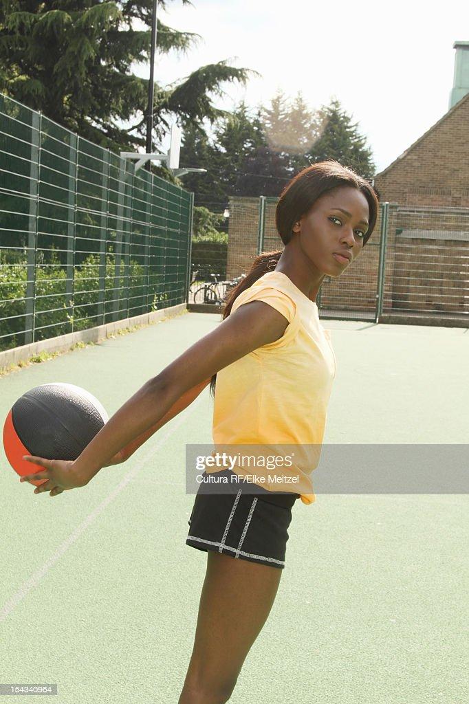 Woman playing basketball on court : Stock Photo