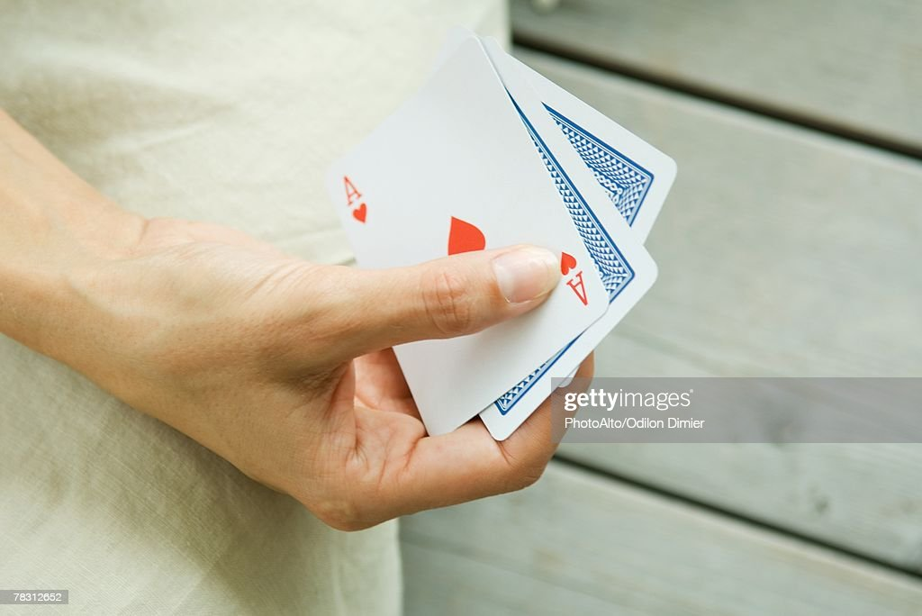 Woman playing card game, cropped view of hand holding cards : Stock Photo