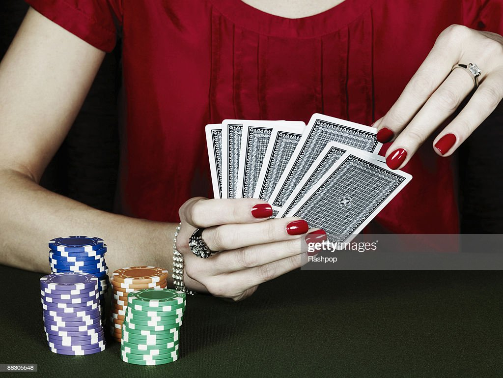 Woman playing cards with poker chips : Stock Photo