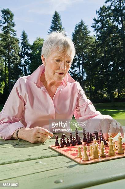 Woman playing chess in park