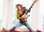 Woman playing electric guitar in sitting room