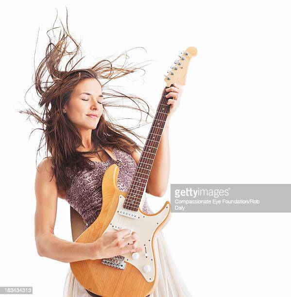 Woman playing electric guitar with hair blowing