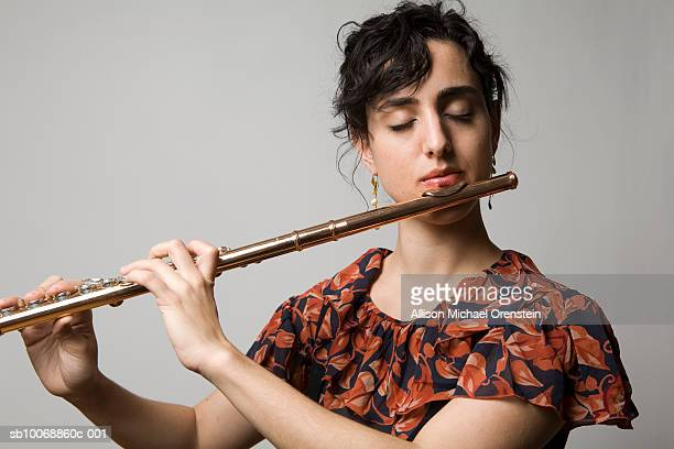 Woman playing flute, eyes closed, close-up