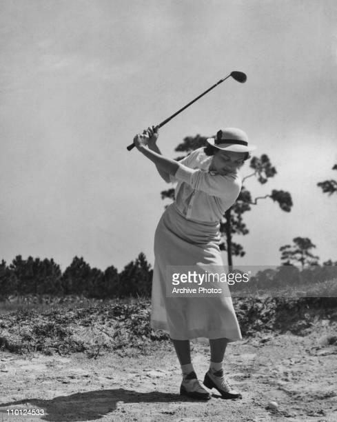 A woman playing golf circa 1940