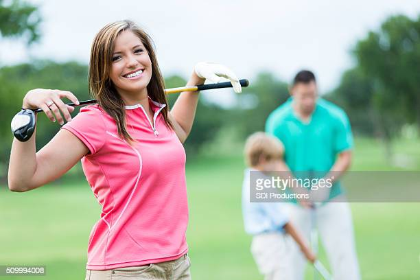 Woman playing golf with family