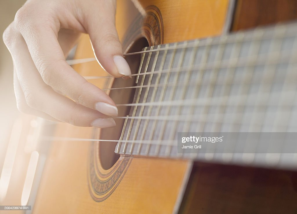 Woman playing guitar, close-up (blurred motion) : Stock Photo