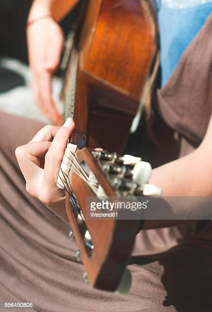 Woman playing guitar, close-up