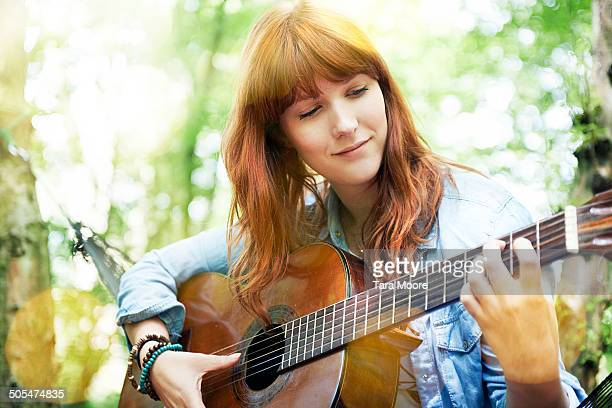 woman playing guitar in forest