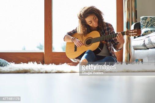 Woman playing guitar in lounge.