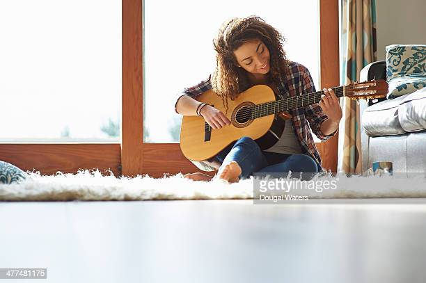 Woman playing guitar in lounge.