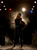 Woman playing guitar on stage, rear view