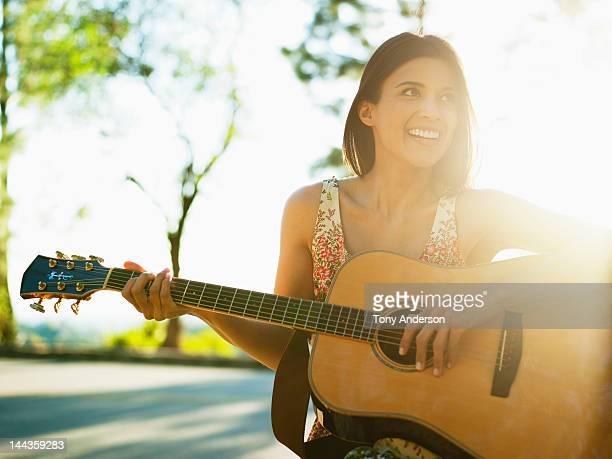 Woman playing guitar outdoors