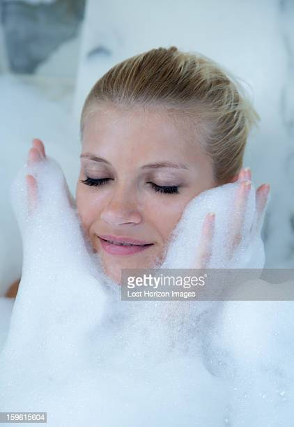 Woman playing in bubble bath