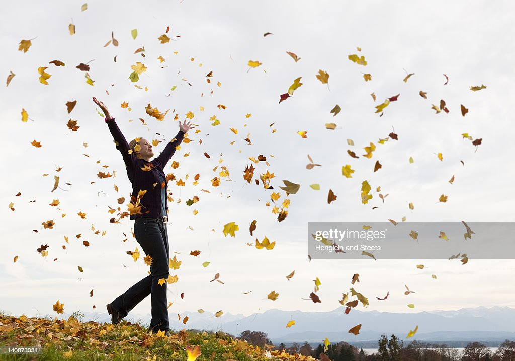 Woman playing in fall leaves : Stock Photo